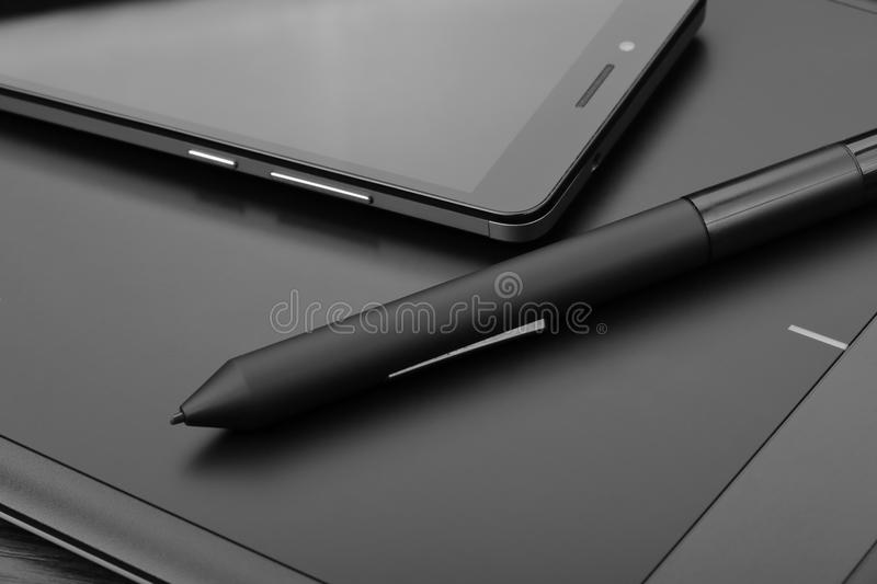 Smartphone and digital drawing tablet also known as a digital art board with a special pen-like stylus on a wooden table. Detail stock photography
