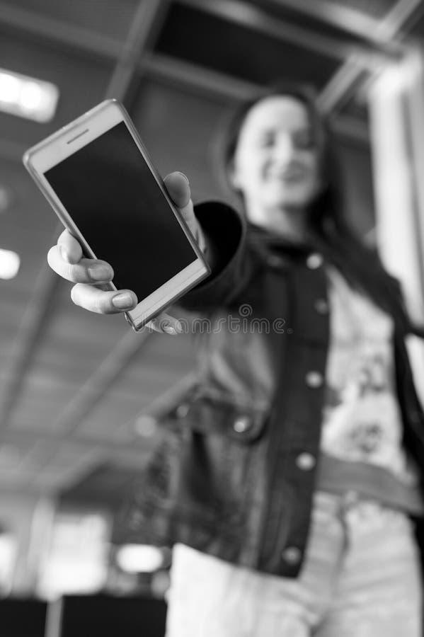 Smartphone a disposición de la muchacha borrosa fotografía de archivo libre de regalías