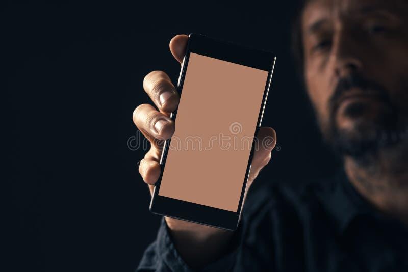 Smartphone do modelo da terra arrendada do homem fotografia de stock