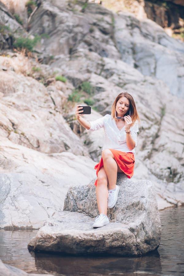 Smartphone do usin da jovem mulher no lago imagens de stock