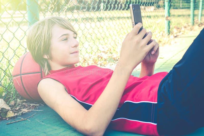 Smartphone do uso do adolescente com os amigos para o basquetebol do jogo exterior - conceito desportivo saudável do estilo de vi foto de stock
