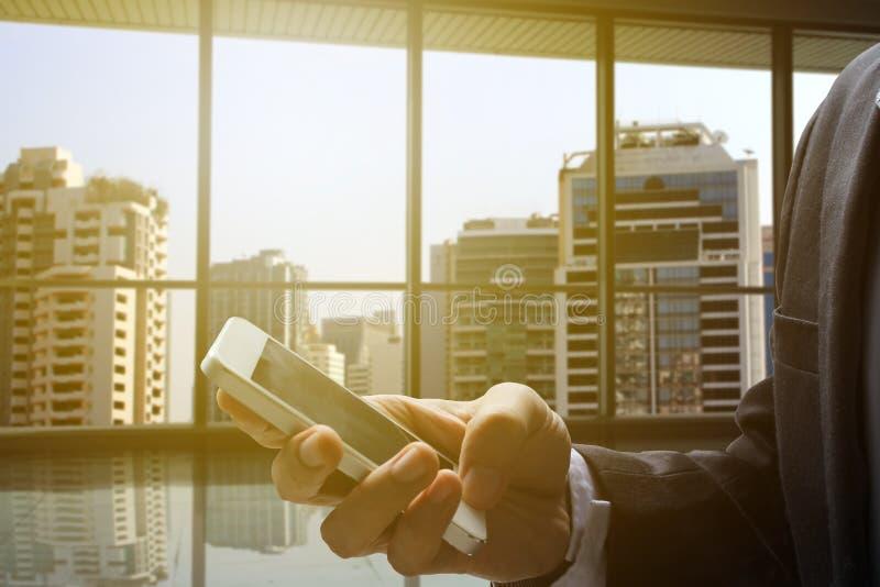 Smartphone do uso da mão do homem de negócios imagens de stock
