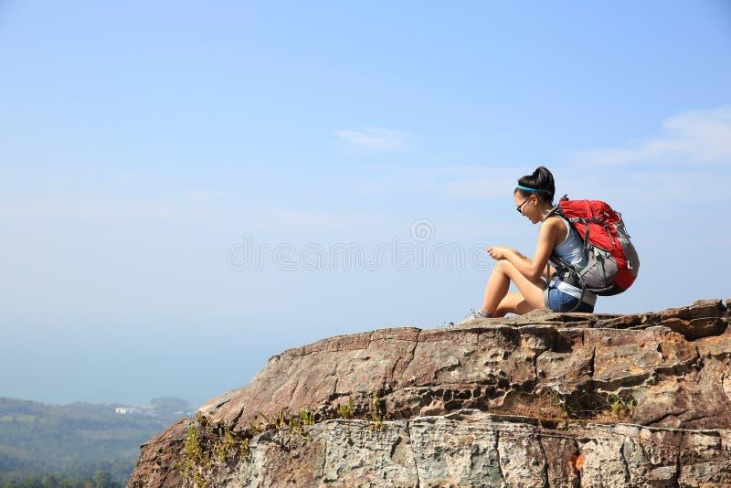 Smartphone do uso do mochileiro da mulher no pico de montanha imagem de stock
