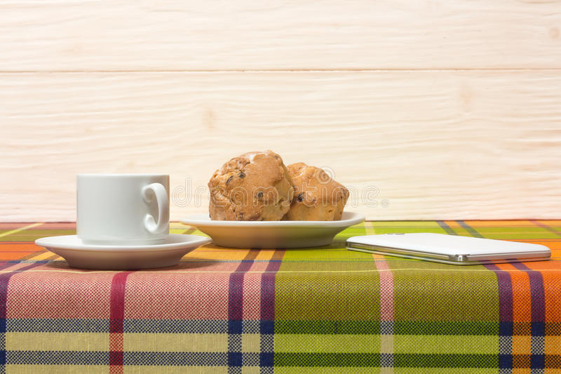 Smartphone dos queques do café na tabela imagens de stock royalty free