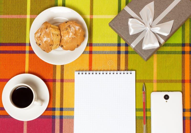 Smartphone dos queques do café na tabela foto de stock royalty free