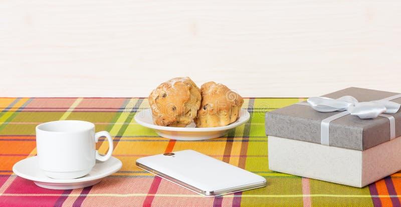 Smartphone dos queques do copo de café na tabela foto de stock
