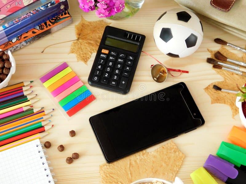 Smartphone e calcolatore circondati dai rifornimenti di scuola immagini stock libere da diritti
