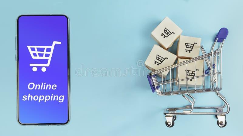 Smartphone e carro com as caixas no fundo azul O conceito na loja do Internet foto de stock royalty free