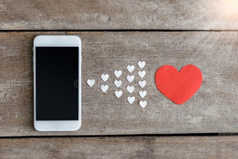 Smartphone e carta dei cuori su fondo di legno immagine stock libera da diritti