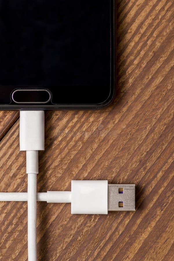 Smartphone e fio de carregamento pretos com o conector do usb no fundo de madeira Telefone celular com a tomada branca da conexão imagem de stock