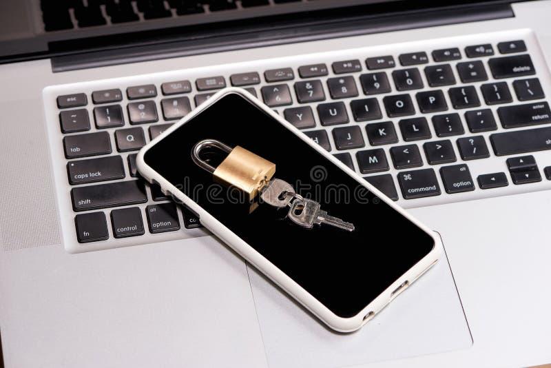Smartphone e o cadeado estão encontrando-se em um teclado do portátil fotos de stock royalty free