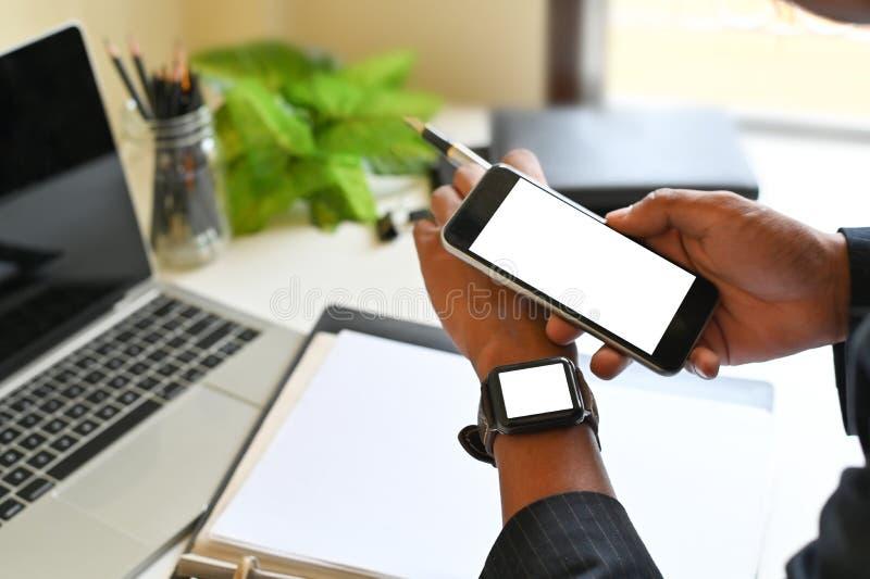 Smartphone e smartwatch em mãos de empresários, zombando de montagens de uma tecnologia móvel imagens de stock royalty free