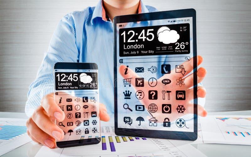 Smartphone e tabuleta com a tela transparente nas mãos humanas. fotos de stock royalty free