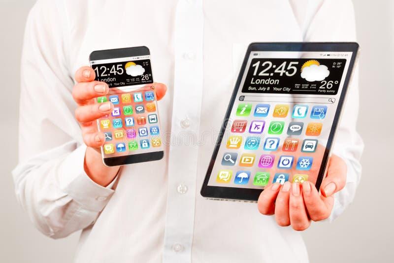Smartphone e tabuleta com a tela transparente nas mãos humanas. fotografia de stock royalty free