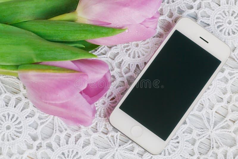 Smartphone e tulipani su una tovaglia di lavorare all'uncinetto immagini stock libere da diritti