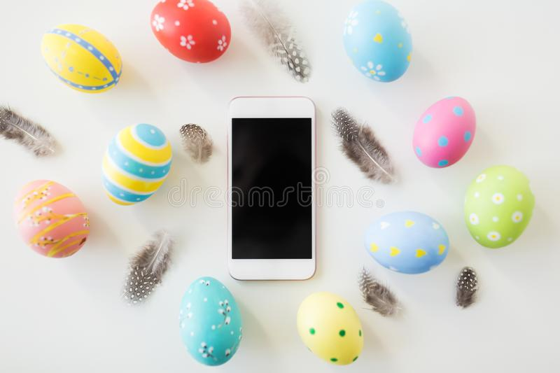 Smartphone with easter eggs and quail feathers royalty free stock images