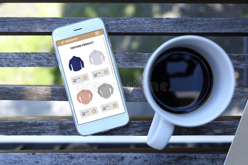 Smartphone with ecommerce website screen and coffee cup royalty free stock photos