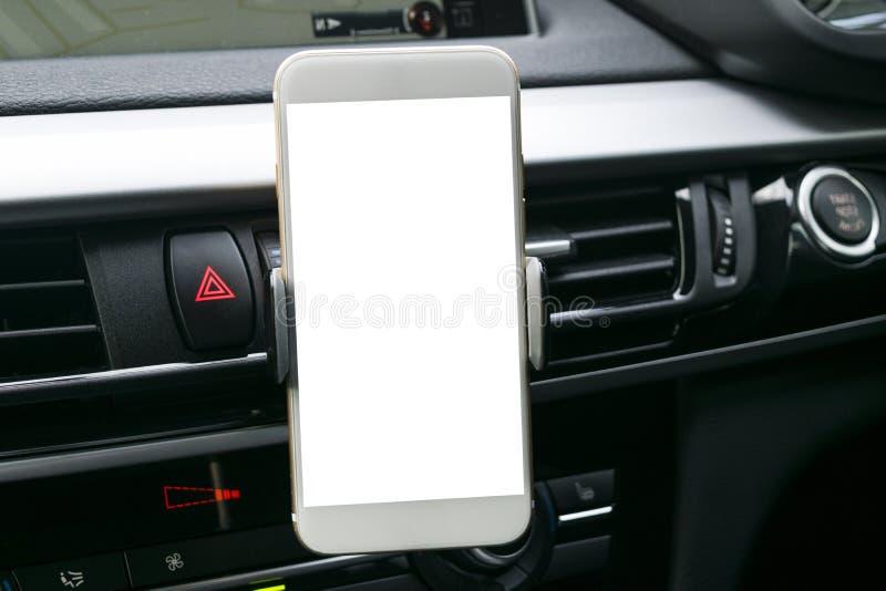 Smartphone in een autogebruik voor Navigate of GPS Het drijven van een auto met Smartphone in houder Mobiele telefoon met het wit stock fotografie