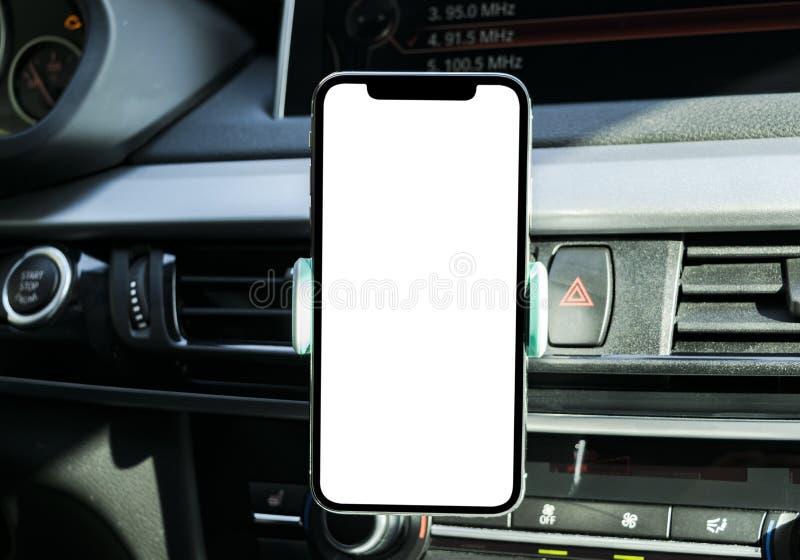 Smartphone in een autogebruik voor Navigate of GPS Het drijven van een auto met Smartphone in houder Mobiele telefoon met het wit royalty-vrije stock foto's