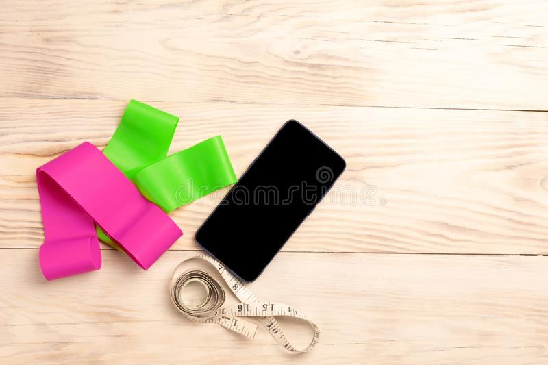 Smartphone, elastic bands for fitness, measuring tape on wooden background. Concept of healthy lifestyle, bodybuilding and weight stock photo