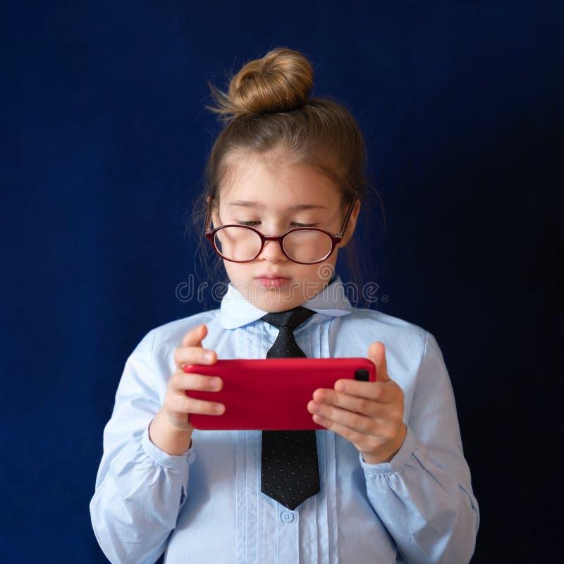 Smartphone elementare della tenuta dello studente del grado fotografia stock libera da diritti