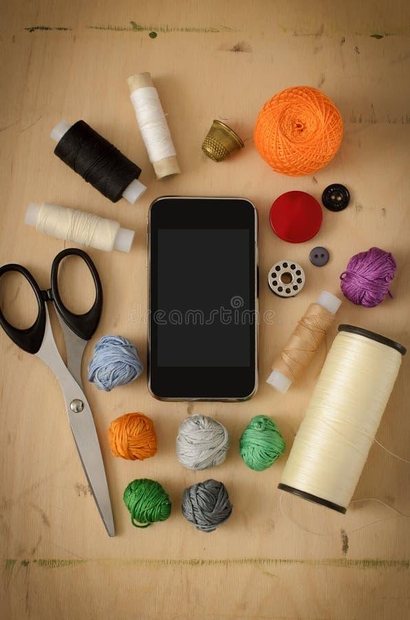 Smartphone em sua costureira do desktop imagens de stock royalty free