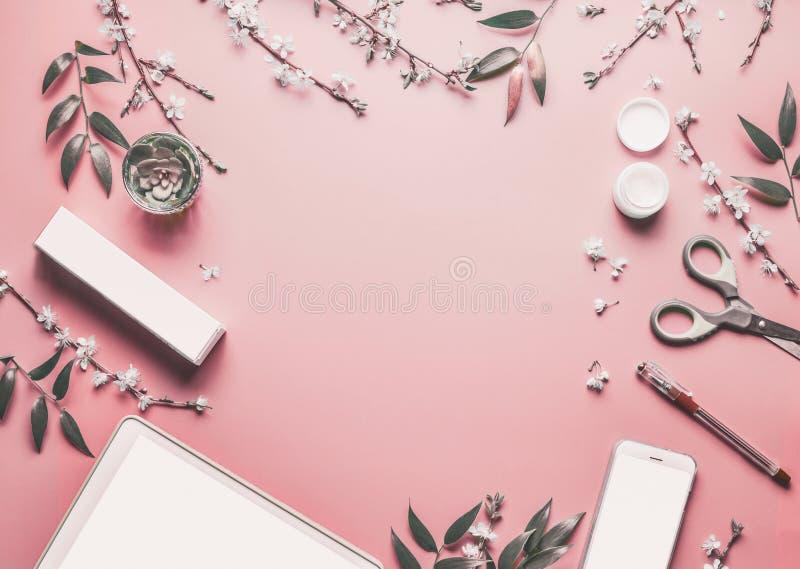 Smartphone en de spot van tabletpc omhoog op achtergrond van de pastelkleur de roze Desktop met moderne schoonheidsmiddelen, kant stock foto's