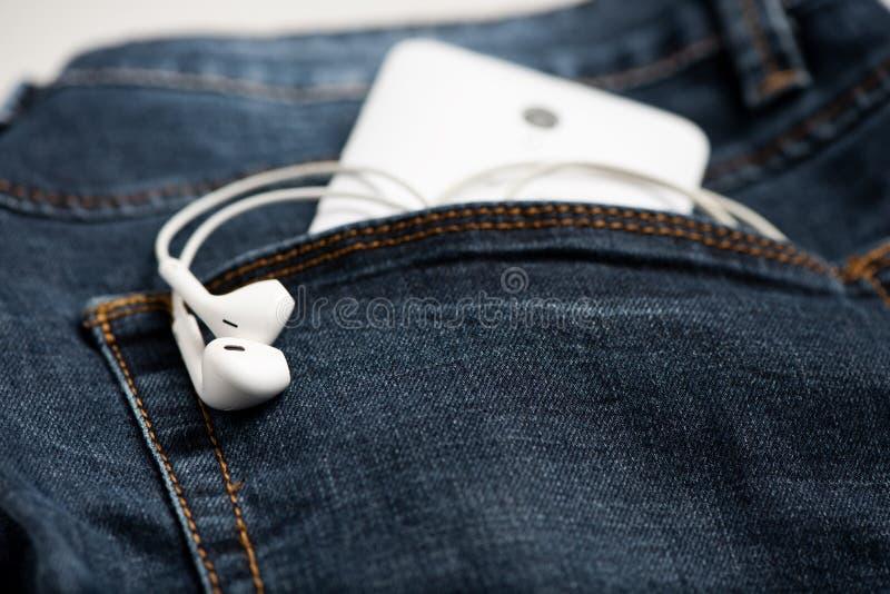 Smartphone en el bolsillo delantero de tejanos y del auricular blanco fotos de archivo libres de regalías