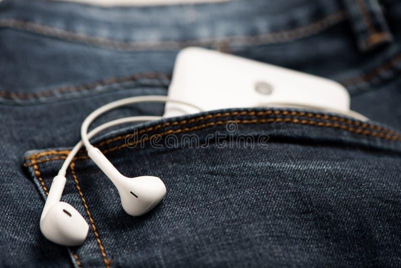 Smartphone en el bolsillo delantero de tejanos y del auricular blanco imágenes de archivo libres de regalías