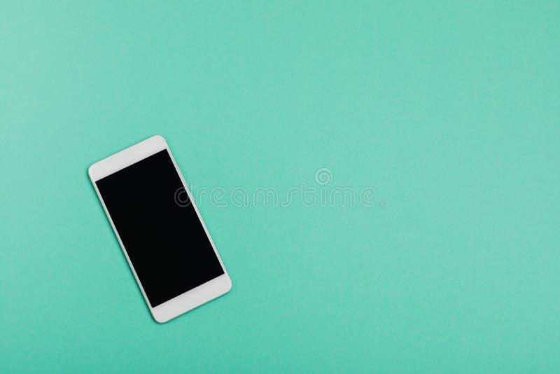 Smartphone en fondo azul usando el papel pintado para la educación, foto del negocio Tome la nota del producto para el concepto m fotografía de archivo