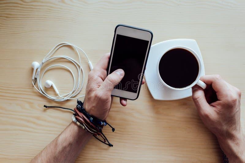 Smartphone en kop van koffie in handen royalty-vrije stock foto