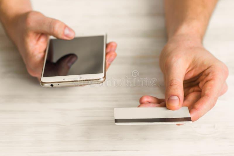 Smartphone en línea del negro de los pagos A y una tarjeta de crédito en las manos de un hombre foto de archivo