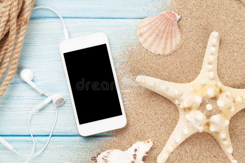 Smartphone en la madera y el arena de mar con las estrellas de mar y las cáscaras fotografía de archivo libre de regalías