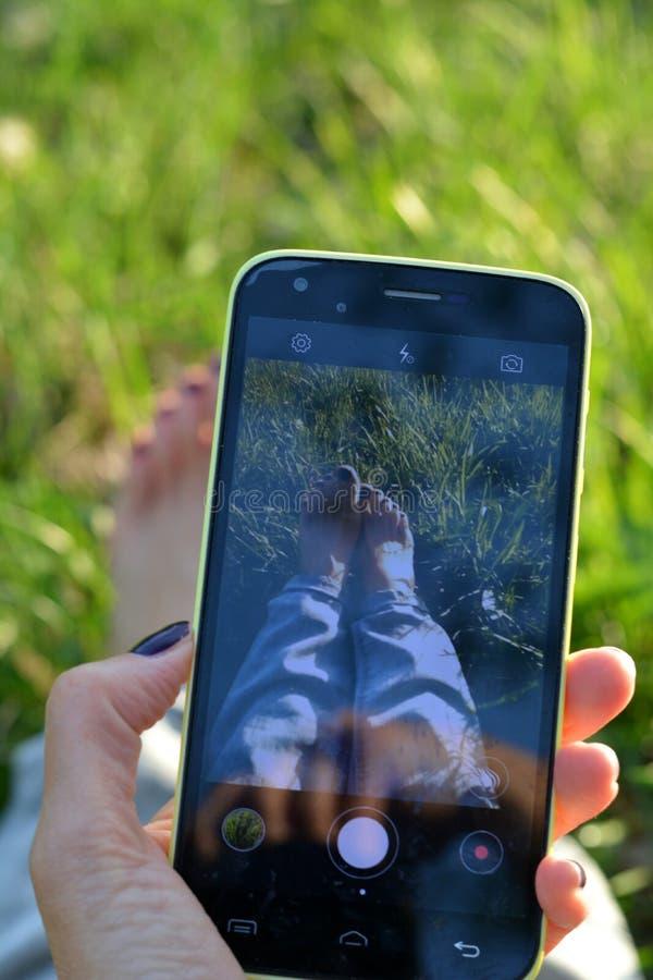 Smartphone en la mano femenina toma a imagen las piernas descalzas fondo de la primavera de la hierba verde fotografía de archivo libre de regalías