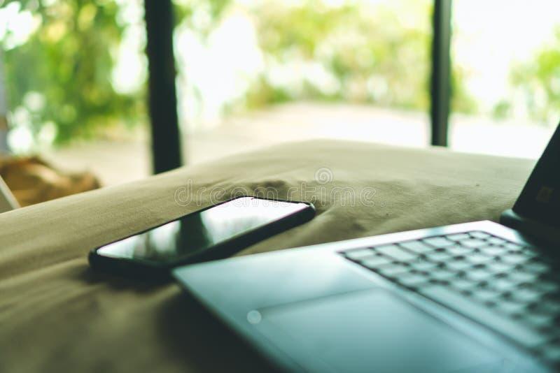Smartphone en laptop op bed royalty-vrije stock afbeeldingen