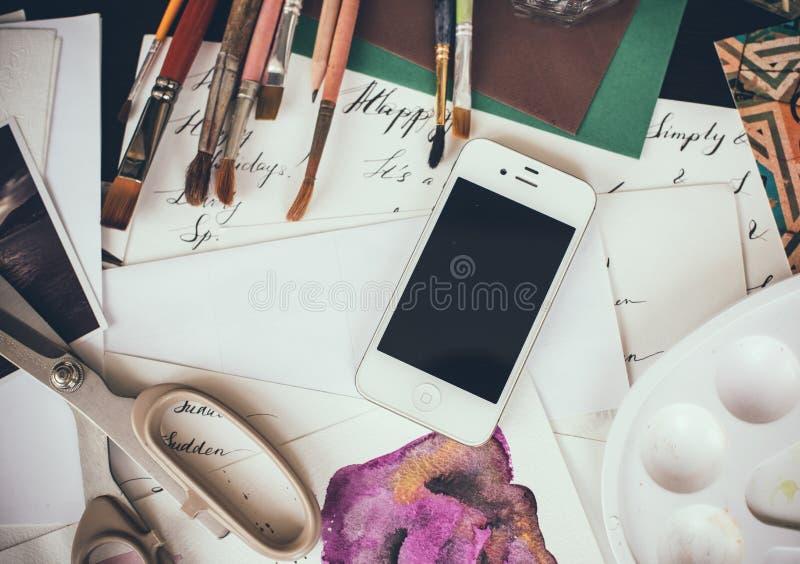Smartphone en una tabla en el estudio del artista fotos de archivo