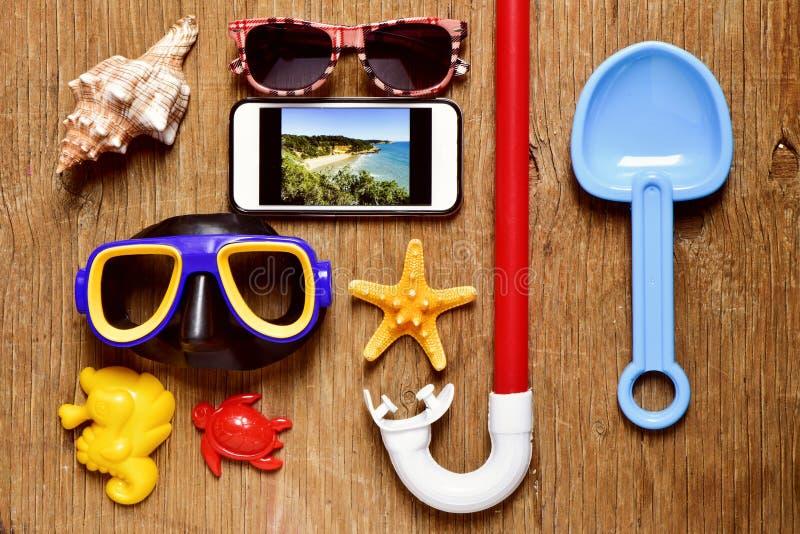 Smartphone en wat de zomermateriaal op een rustieke houten lijst stock fotografie