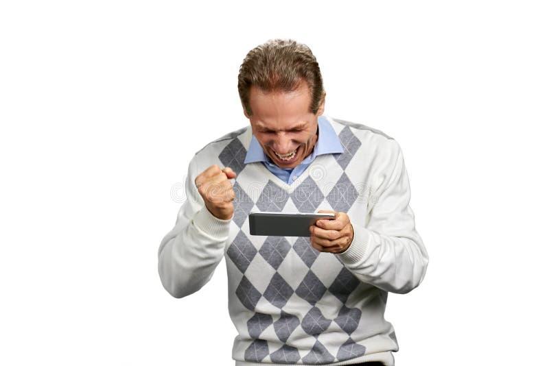 Smartphone entusiasmado da terra arrendada do punho apertado do homem fotos de stock
