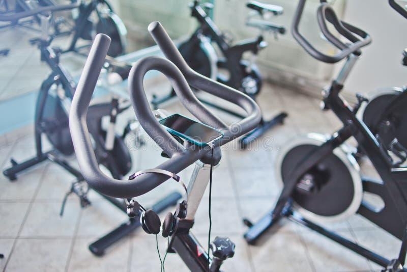 Smartphone et écouteurs accrochant sur le vélo stationnaire à la classe de rotation photo libre de droits