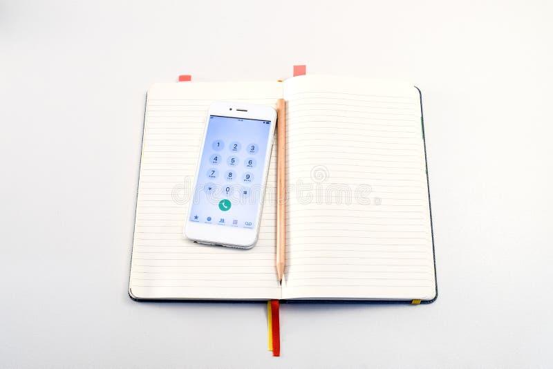 Smartphone et crayon dans le livre sur la table blanche photographie stock libre de droits