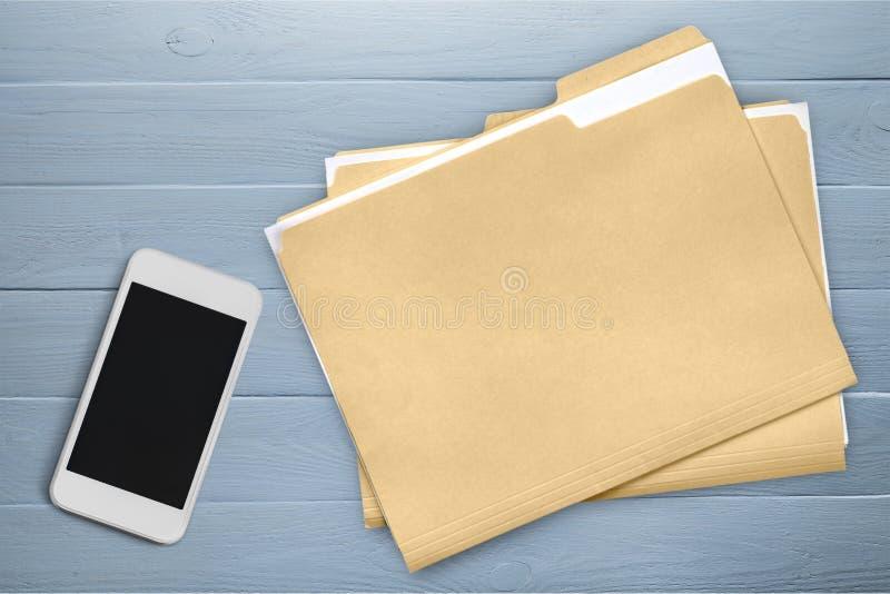 Smartphone et dossiers de document sur en bois photographie stock libre de droits