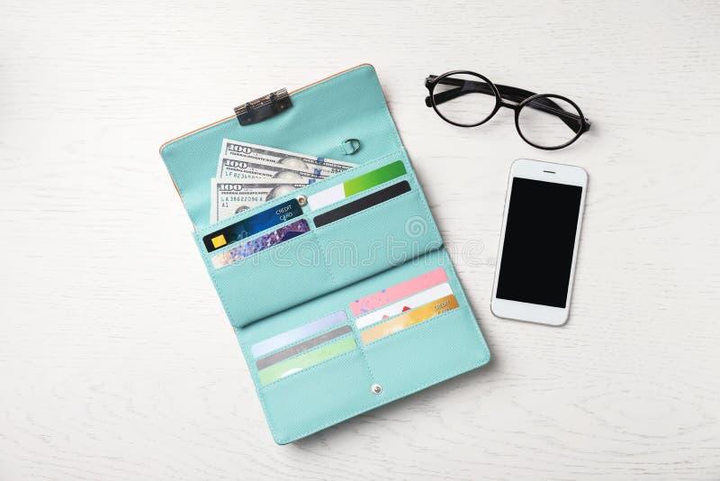 Smartphone, exponeringsglas och stilfull plånbok med kassa royaltyfria foton
