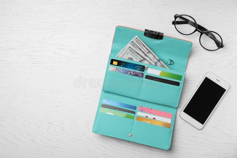 Smartphone, exponeringsglas och stilfull plånbok med kassa arkivfoton