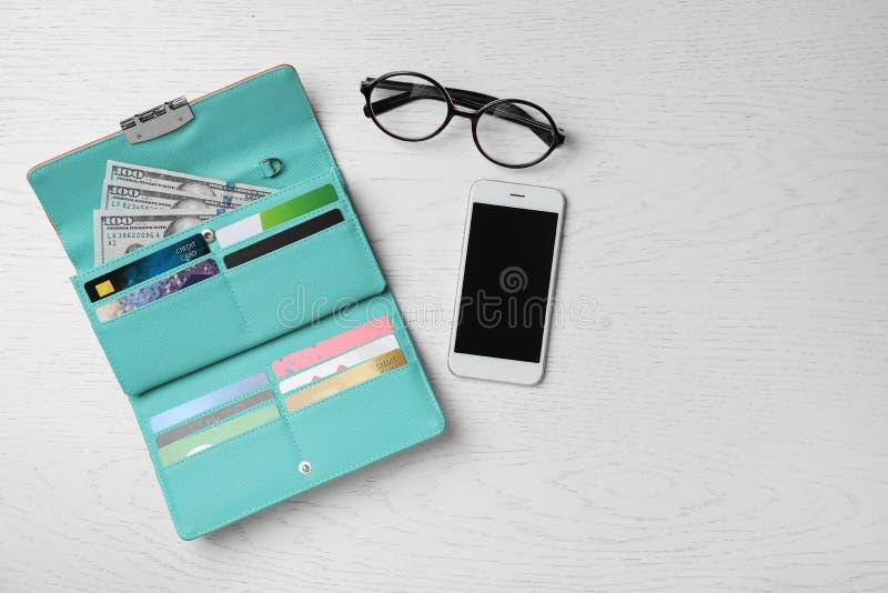 Smartphone, exponeringsglas och stilfull plånbok med kassa royaltyfri bild