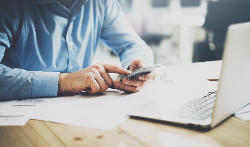 Smartphone för affärsmanmaskinskrivningtext Generisk designbärbar dator på tabellen Suddig bakgrund, horisontalmodell fotografering för bildbyråer