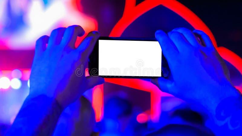 Smartphone för handkonturinnehav med vit tom skärm på konserten fotografering för bildbyråer