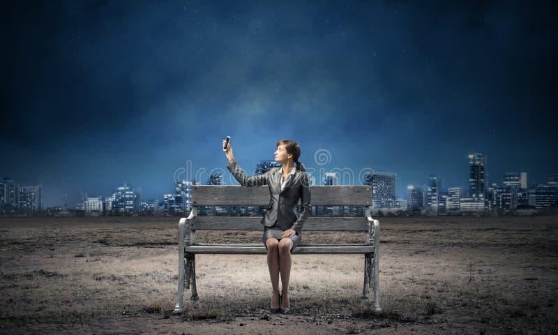 Smartphone för innehav för affärskvinna med den lyftta handen royaltyfri bild