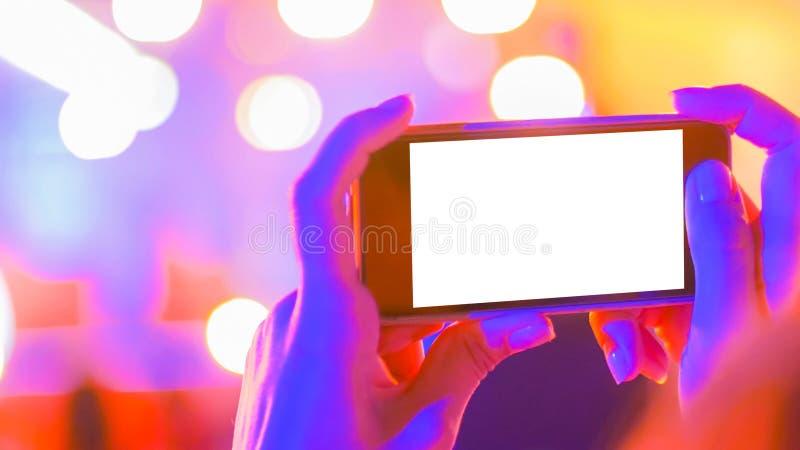Smartphone för innehav för kvinnahandkontur med vit tom skärm på konserten arkivbild