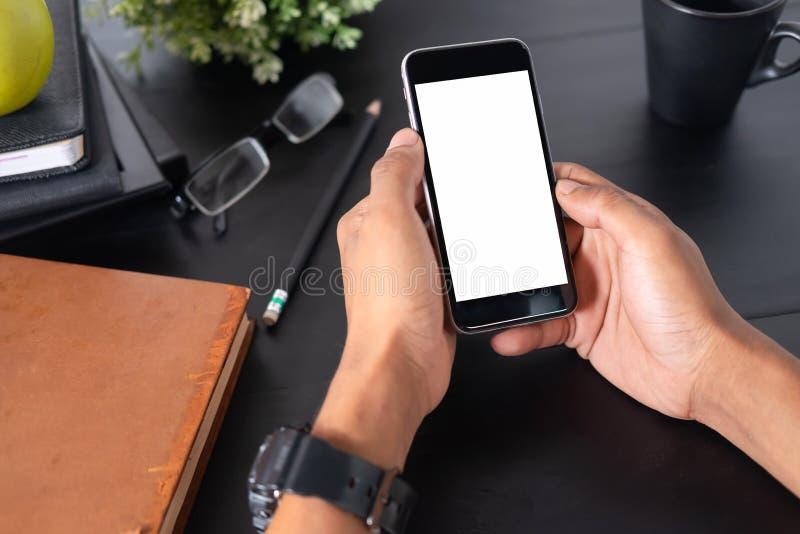 Smartphone för maninnehavmodell på svart tabellkontorsworkspace arkivbild