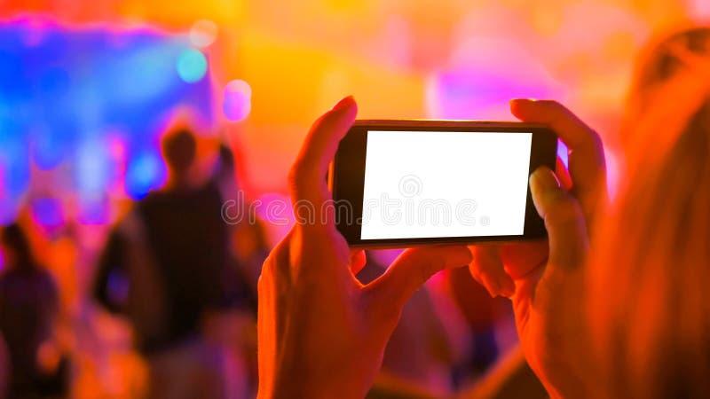 Smartphone f?r innehav f?r kvinnahandkontur med vit tom sk?rm p? konserten arkivbild